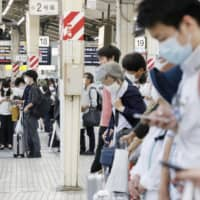 People wait to get on a shinkansen at Tokyo Station on Friday. | KYODO