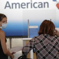 Travelers wait at the American Airlines ticket counter at Chicago's O'Hare Airport. The airline has banned a passenger who refused to wear a mask on a recent flight .  | AP