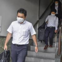 Officials of the prosecutor's office leave after searching Anri Kawai's office in the city of Hiroshima on Friday. | KYODO