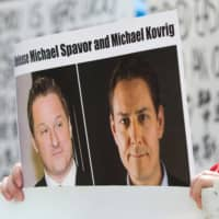 A protester against China's treatment of Uighurs holds a photo of detained Canadians Michael Spavor (left) and Michael Kovrig. China has begun the prosecution of two Canadian nationals detained since December 2018 on spying charges, officials said Friday.  | AFP-JIJI