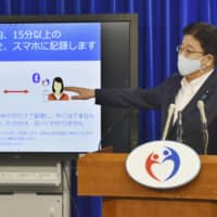 Health minister Katsunobu Kato explains the ministry's contact-tracing app on Friday. | KYODO