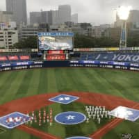 The BayStars and Carp stand on the field during a pregame ceremony on Friday at Yokohama Stadium. | JASON COSKREY
