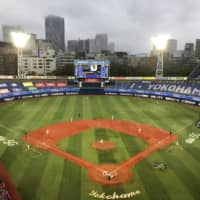 The BayStars and Carp play under the lights at Yokohama Stadium on Friday after their season opener was delayed 30 minutes by rain. | JASON COSKREY