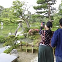 A woman snaps a photo at Kenrokuen, one of Japan's three most famous gardens, in Kanazawa, Ishikawa Prefecture, on Saturday, a day after the government lifted its last-remaining advisories recommending against inter-prefecture travel amid the coronavirus pandemic. | KYODO