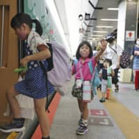 Children board a Tohoku Shinkansen Line bullet train at Tokyo Station on Saturday, a day after the government lifted its last-remaining advisories recommending against inter-prefecture travel amid the coronavirus pandemic. | KYODO