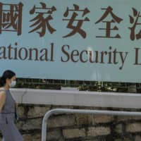 A woman walks past a government-sponsored advertisement promoting a new national security law China plans to enact, in Hong Kong on Friday.   BLOOMBERG