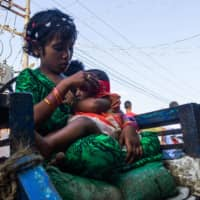 A girl holds a baby in Sittwe in Myanmar's Rakhine state on May 24.  | AFP-JIJI