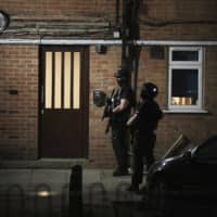 Armed police officers stand near a block of flats in Reading, England, after several people were injured in a stabbing attack at Forbury Gardens park.    PA / VIA AP