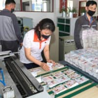 This undated picture released Saturday shows North Koreans preparing anti-Seoul leaflets that will be sent into the South as tensions soar on the Korean Peninsula. | KCNA / KNS / VIA AFP-JIJI