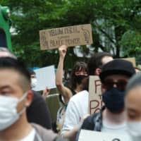 A protester holds a sign during a march again police brutality and racism toward foreign residents of Japan on June 6 in Tokyo's Shibuya Ward. | RYUSEI TAKAHASHI
