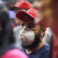 A supporter of U.S. President Donald Trump wears a protective face mask during a campaign rally in Tulsa, Oklahoma, on Saturday. | REUTERS