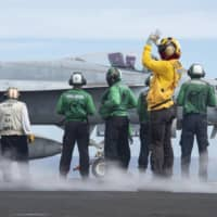 Sailors prepare to launch an F/A-18E Super Hornet from the flight deck of the U.S. Navy's only forward-deployed aircraft carrier, the USS Ronald Reagan, during flight operations on Thursday in the Philippine Sea. | U.S. NAVY