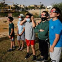 Boys wear special protective glasses as they observe the eclipse from Yeruham, southern Israel.  | REUTERS