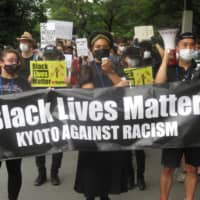 Participants of Black Lives Matter march in Kyoto hold a banner on Sunday.  | ERIC JOHNSTON