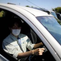 Ryota Kawamata says driving a rented car to work during the pandemic has motivated him to buy his own vehicle.  | REUTERS