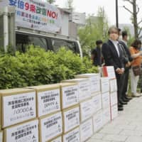 A civic group opposing the revision to war-renouncing Article 9 of the Constitution holds a rally in Tokyo with boxes containing more than 240,000 signatures on June 4. | KYODO