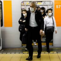 Passengers get off a subway train at Tokyo's Shibuya station. More than 60 percent of Japanese workers who have worked from home during the COVID-19 crisis say they want to do so after the pandemic has passed. | REUTERS
