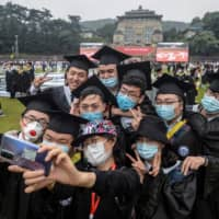 Students in Wuhan, China, where COVID-19 was first detected, donned face masks for their graduation ceremonies, joining many around the world for whom masks have become essential. | STR / AFP-JIJI / CHINA OUT