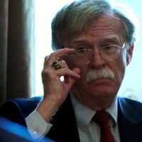 Then-U.S. national security adviser John Bolton listens as President Donald Trump holds a Cabinet meeting at the White House in Washington in April 2018. | REUTERS