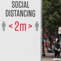 A sign urges 2 meters of social distancing in London on Monday.  | AP