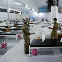 Workers prepare a bed at a recently constructed quarantine facility for COVID-19 patients in Mumbai on Monday.  | REUTERS