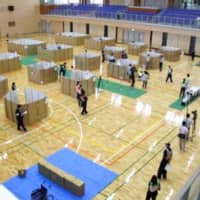 Officials use cardboard to maintain social distancing during a drill to practice setting up an evacuation center in Mashiki, Kumamoto Prefecture, in May. | THE TOWN OF MASHIKI / VIA KYODO