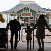 A family looks at the entrance of Tokyo Disneyland on Feb. 29, the first day the facility was closure due to the coronavirus. | KYODO