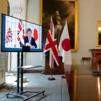 U.K. International Trade Secretary Liz Truss, right, holds a video conference call with Japan's Foreign Minister Toshimitsu Motegi as they formally begin negotiations on a free trade agreement at the Department for International Trade in London on June 9. | 10 DOWNING STREET / ANDREW PARSONS / VIA AFP-JIJI