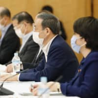 Chief Cabinet Secretary Yoshihide Suga (center) on Tuesday addresses the first meeting of a government working group established to discuss ways to promote My Number cards, at the Prime Minister's Office. | KYODO