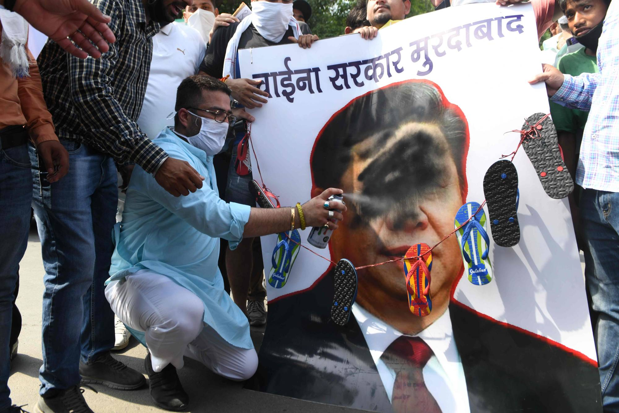 Activists spray black paint on a poster depicting Chinese President Xi Jinping during an anti-China protest in Amritsar, India, on Monday.  | AFP-JIJI