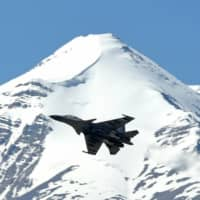 An Indian fighter jet flies over a mountain range near Leh on Tuesday.  | AFP-JIJI