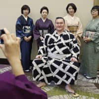 Yokozuna Hakuho takes a picture with fans before the Nagoya Grand Sumo Tournament in June of 2019, in Nagoya. It is unclear when, or if, this type of interaction between fans and rikishi will return even after the COVID-19 pandemic. | KYODO