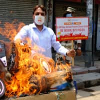 Protesters burn an image of Chinese President Xi Jinping at a demonstration requesting consumers to boycott Chinese goods in New Delhi on Monday. | BLOOMBERG