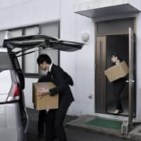 Investigators carry boxes from the office of Katsuyuki Kawai in Hiroshima during a raid in January. | KYODO