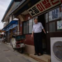 North Korean refugee Ji Gwang-sik stands at the door to his barber shop on the western island of Gyodong. He was 13 when he fled Yonpek, his North Korean hometown, at the height of the conflict. | AFP-JIJI