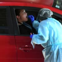 Medical workers staff a drive-thru COVID-19 testing site in Melbourne on Tuesday.   AFP-JIJI