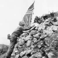 A U.S. Marine climbs the rubble of Shuri Castle, which was bombed by the U.S. military, to raise an American flag in Naha, Okinawa Prefecture, in June 1945. | ACME / VIA KYODO