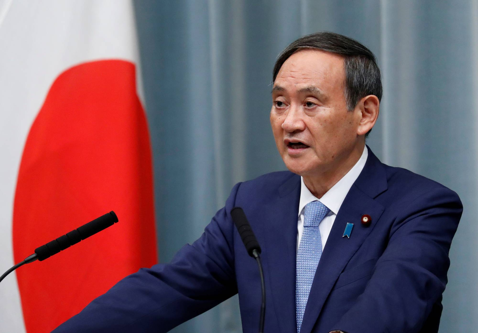 Chief Cabinet Secretary Yoshihide Suga said Wednesday that under the Constitution, striking an enemy base is allowed for self-defense if there are no other means. Suga made the remarks on the same day China asked Japan to maintain its 'exclusively defense-oriented' policy.    REUTERS