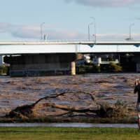 A man takes a picture of the Tama river, which reached flood risk level due to Typhoon Hagibis, in Tokyo in October 2019. | REUTERS