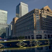 Pedestrians cross a footbridge in view of buildings in the West India Dock in the Canary Wharf financial district in London. | BLOOMBERG
