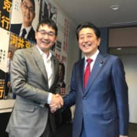 A photo posted on Katsuyuki Kawai's Facebook page shows him shaking hands with Prime Minister Shinzo Abe in Tokyo in September 2018. | KYODO