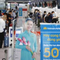 About 150 people took a charted flight from Japan's Narita International Airport to Van Don International Airport in Vietnam on Thursday.  People check in at Narita International Airport in Chiba Prefecture on Thursday before boarding a chartered flight to Vietnam's Van Done. | KYODO