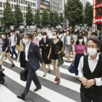 People walk on a busy crossing in the Shinjuku Ward of Tokyo on Thursday.   KYODO