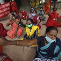 Female domestic workers, many of whom have lost their jobs after the coronavirus outbreak, demand social security benefits from the government in Bengaluru, India, earlier this month. | AP