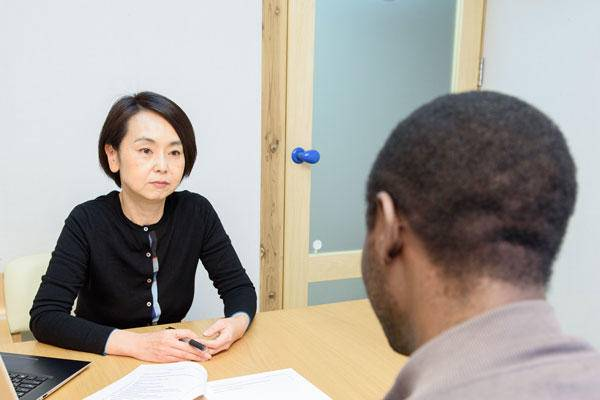 Seeking support: Japan Association for Refugees staff member Ayako Niijima speaks with a refugee during a meeting.  | KYODO