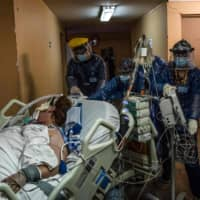 Nurses transfer a COVID-19 patient to the Critical Patients Unit at Barros Luco Hospital in Santiago, Chile, on Wednesday. | AFP-JIJI