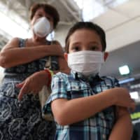 A child and his grandmother hold their arms after receiving a vaccination for the seasonal flu as a preventive measure due to the outbreak of the coronavirus, in Santiago, Chile, in March. | REUTERS