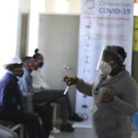 A medical worker addresses vaccine volunteers at a hospital in Soweto, Johannesburg, on Wednesday. | AP