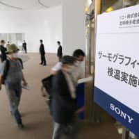 Shareholders of Sony Corp. enter the venue of their annual meeting held at a Tokyo hotel Friday, with a sign warning against coronavirus infection put up at the entrance.   | KYODO