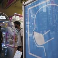 A sign to wear a protective mask to help curb the spread of the new coronavirus is seen at the entrance to a game center in Tokyo on Friday. | AP